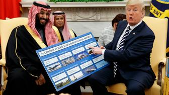 FILE - In this Tuesday, March 20, 2018 file photo, President Donald Trump holds a chart highlighting arms sales to Saudi Arabia during a meeting with Saudi Crown Prince Mohammed bin Salman in the Oval Office of the White House in Washington. (AP Photo/Evan Vucci)