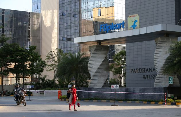 A motorist and a woman walks past a building that formerly was the Flipkart headquarters in Bangalore,...