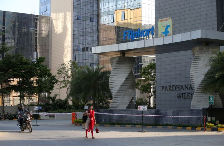 A motorist and a woman walks past a building that formerly was the Flipkart headquarters in Bangalore, India, Wednesday, May