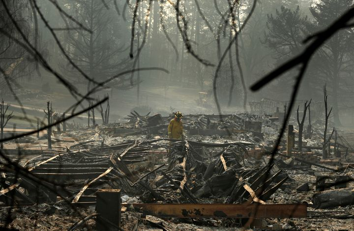 A firefighter searches for human remains in a trailer park destroyed in the Camp Fire, Friday, Nov. 16, 2018, in Paradise, Ca