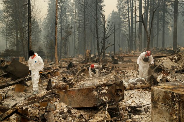 Search and rescue workers search for human remains at a trailer park burned by the Camp Fire in Northern