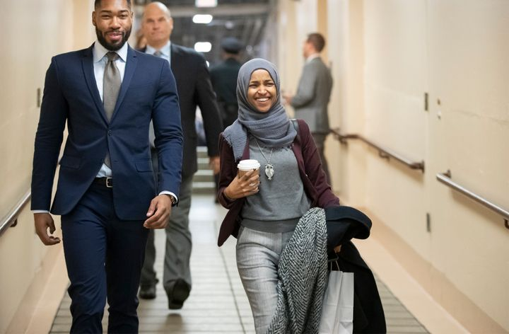 Rep.-elect Ilhan Omar, D-Minn., center, heads to a Democratic Caucus meeting in the basement of the Capitol as new members of