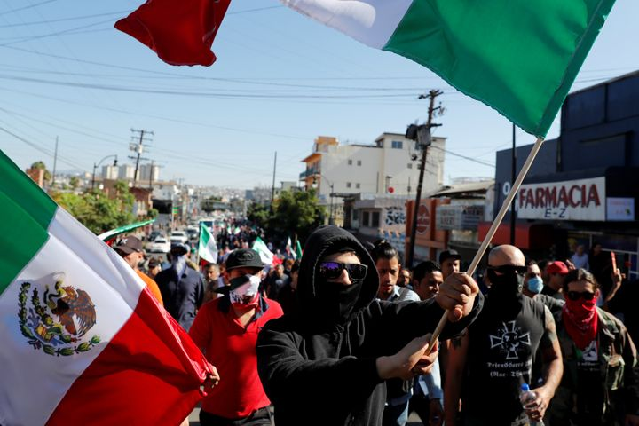 Demonstrators wave Mexican flags during a protest against migrants who are part of a caravan traveling en route to the United