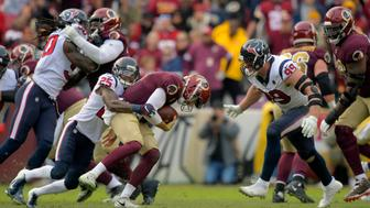 LANDOVER, MD - NOVEMBER 18: Washington Redskins quarterback Alex Smith (11), center, is sacked and injured by Houston Texans defensive end J.J. Watt (99), right, Houston Texans strong safety Kareem Jackson (25)  during a game between the Washington Redskins  and the Houston Texans at FedEX Field on November 18, 2018, in Landover, MD. (Photo by John McDonnell/The Washington Post via Getty Images)