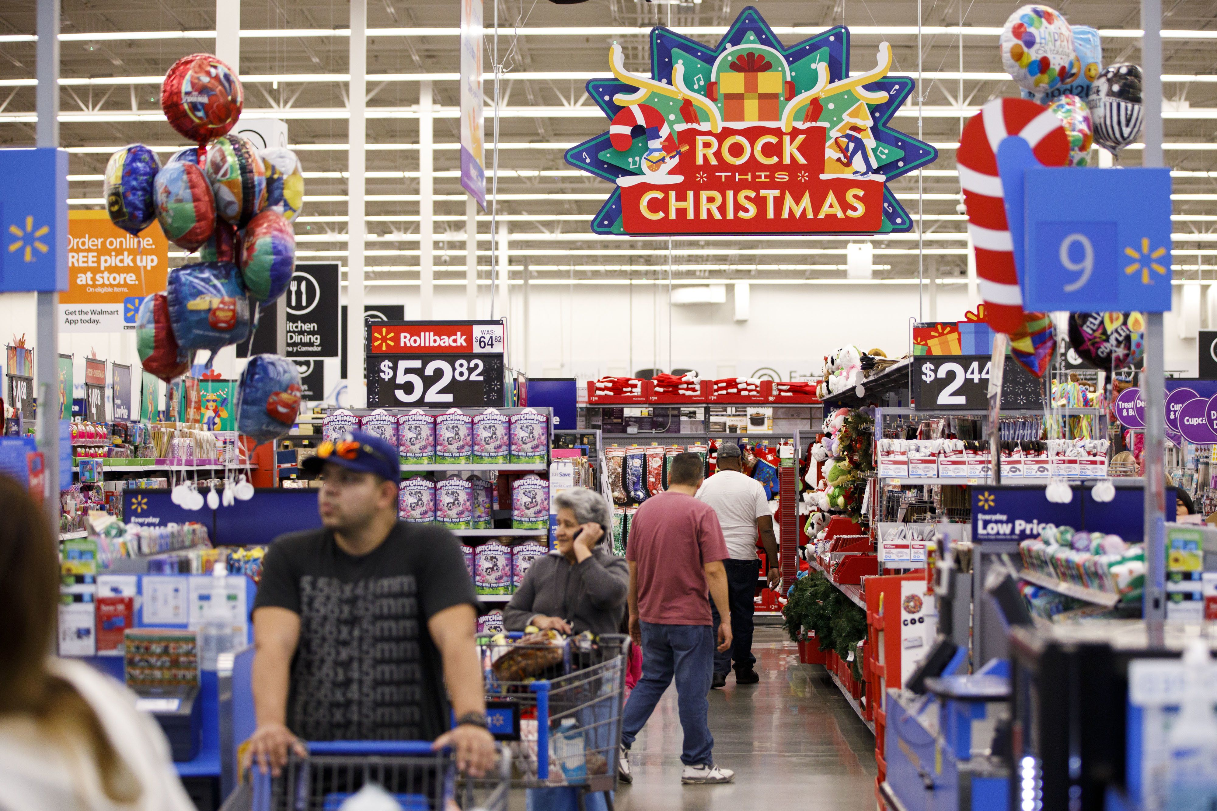 Christmas signage is displayed as customers shop at a Wal-Mart Stores Inc. location in Burbank, California, U.S., on Thursday, Nov. 16, 2017. Black Friday, the day after Thanksgiving, marks the traditional start to the U.S. holiday shopping season. Photographer: Patrick T. Fallon/Bloomberg via Getty Images