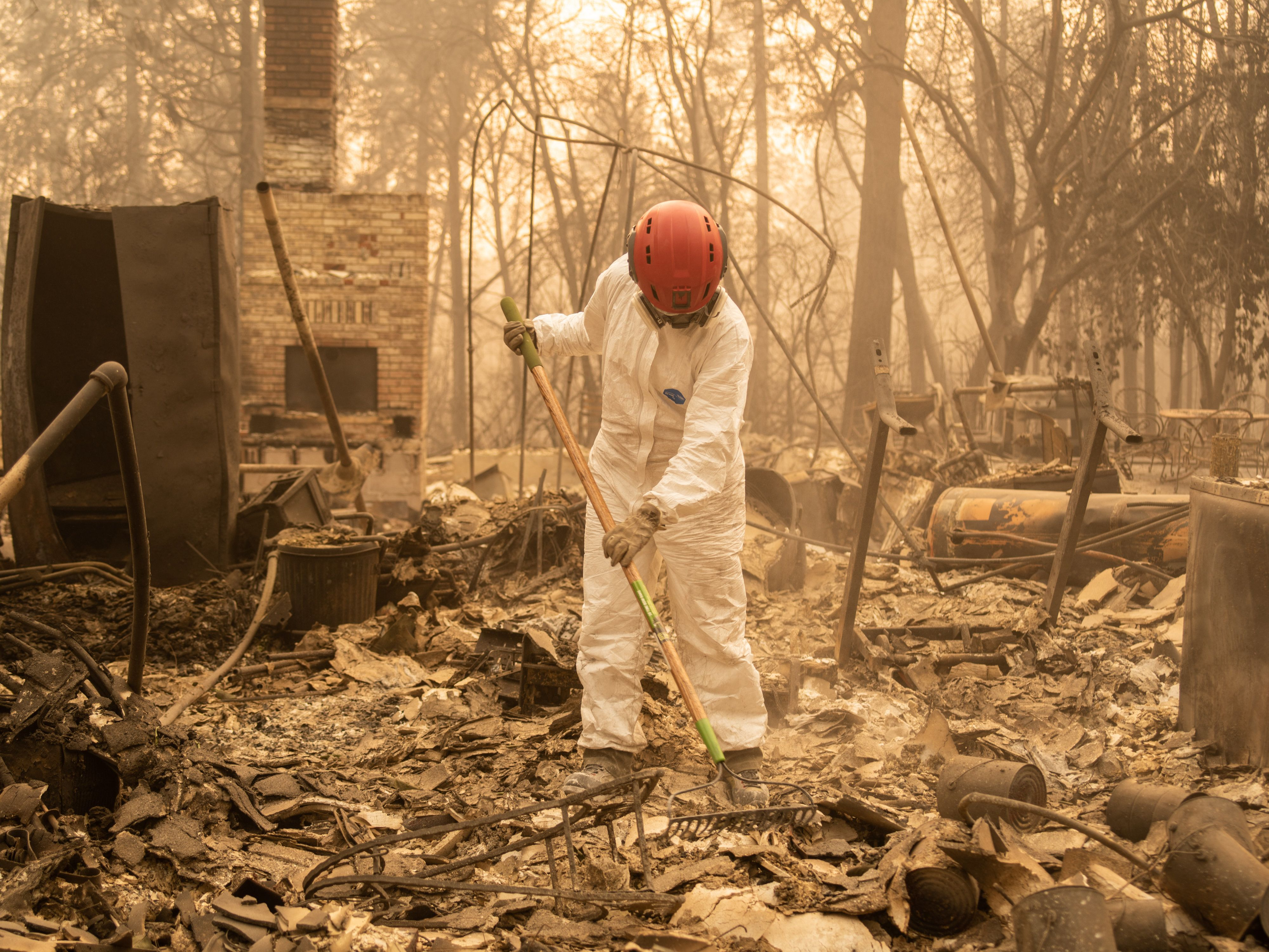 A member of the Tuolumne Sheriff Search & Rescue team searches for human remains at a home in Paradise.