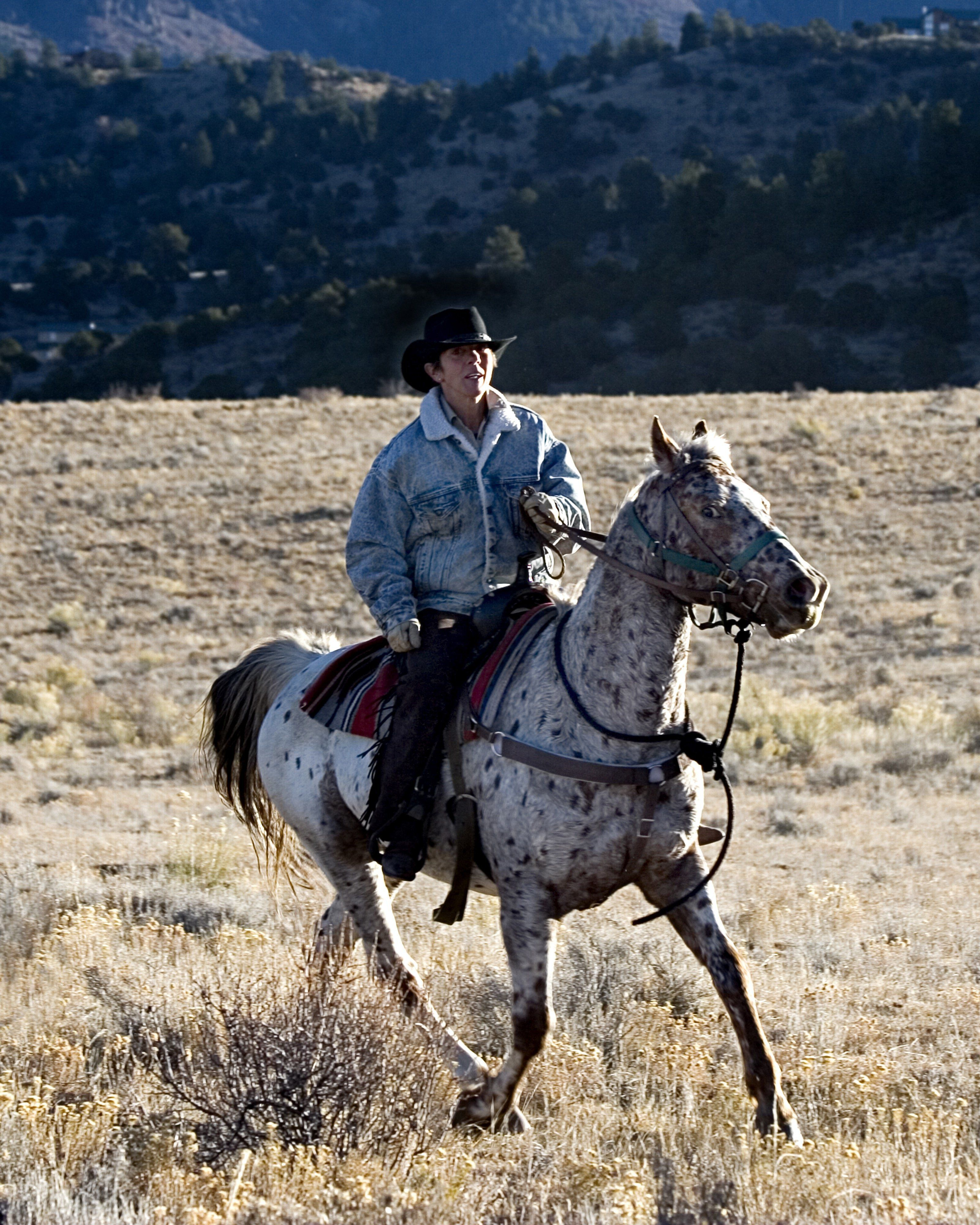 Phyllis rides Spike,an Arabian mare, on a ranch in southern Colorado in 2005.