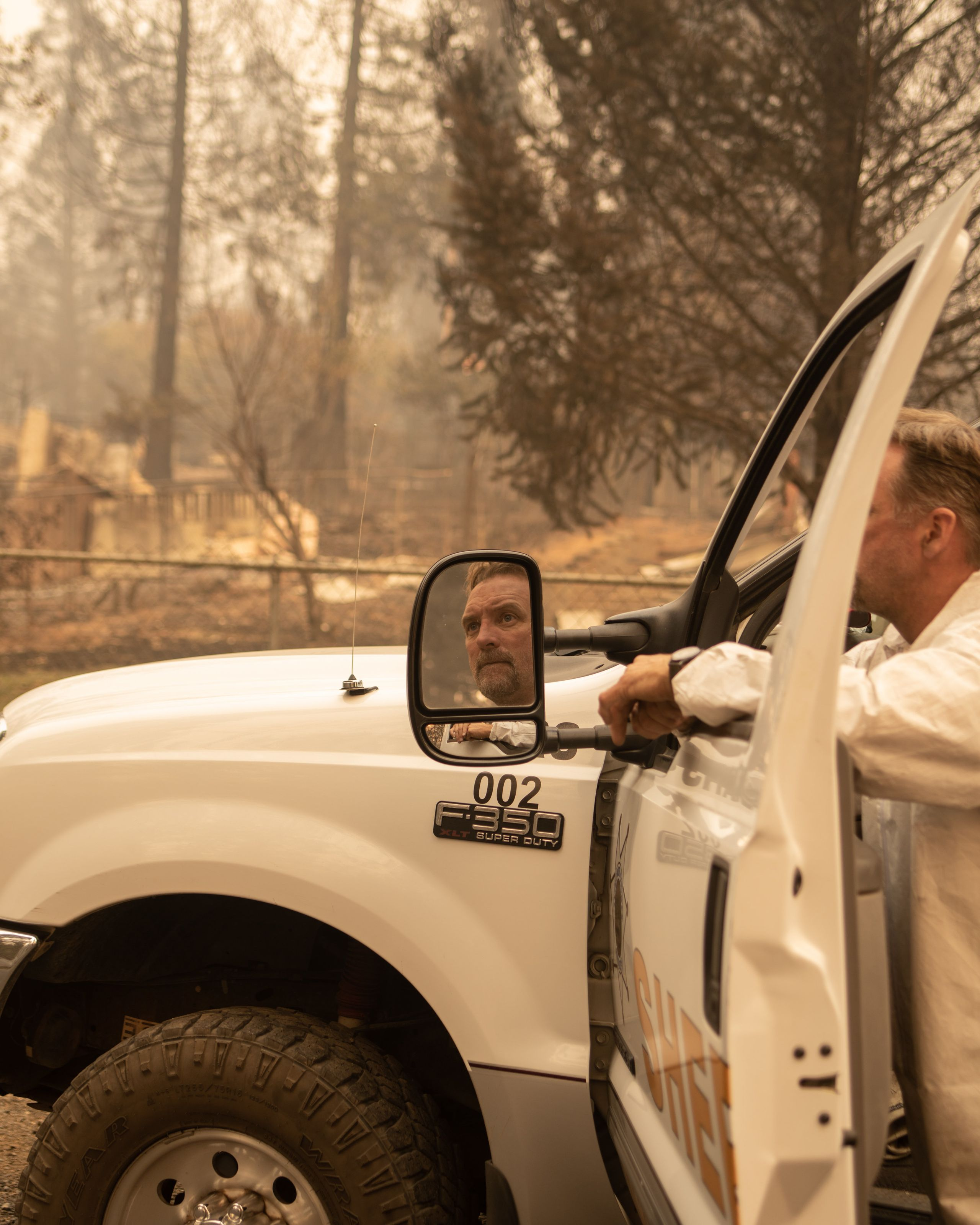 A member of the Tuolumne Sheriff Search & Rescue team looks down the street of a neighborhood in Paradise that was destro
