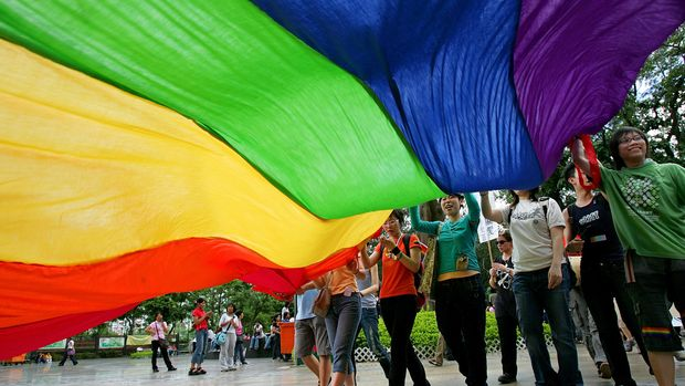 Young participants wave rainbow-colored flag, a symbol of the gay rights movement during a parade at a downtown Hong Kong street Monday, May 16, 2005. Hundreds of gay rights supporters marched against homophobia and discrimination of sexual minorities. (AP Photo/Vincent Yu)