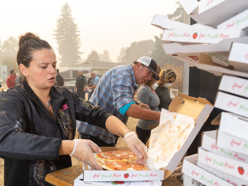 Rolling Stone mobile pizza chef Jim King works with other volunteers to distribute pizzas at the East...