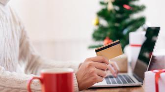 Man holding credit card and doing shopping online. New year, Christmas gift shopping.