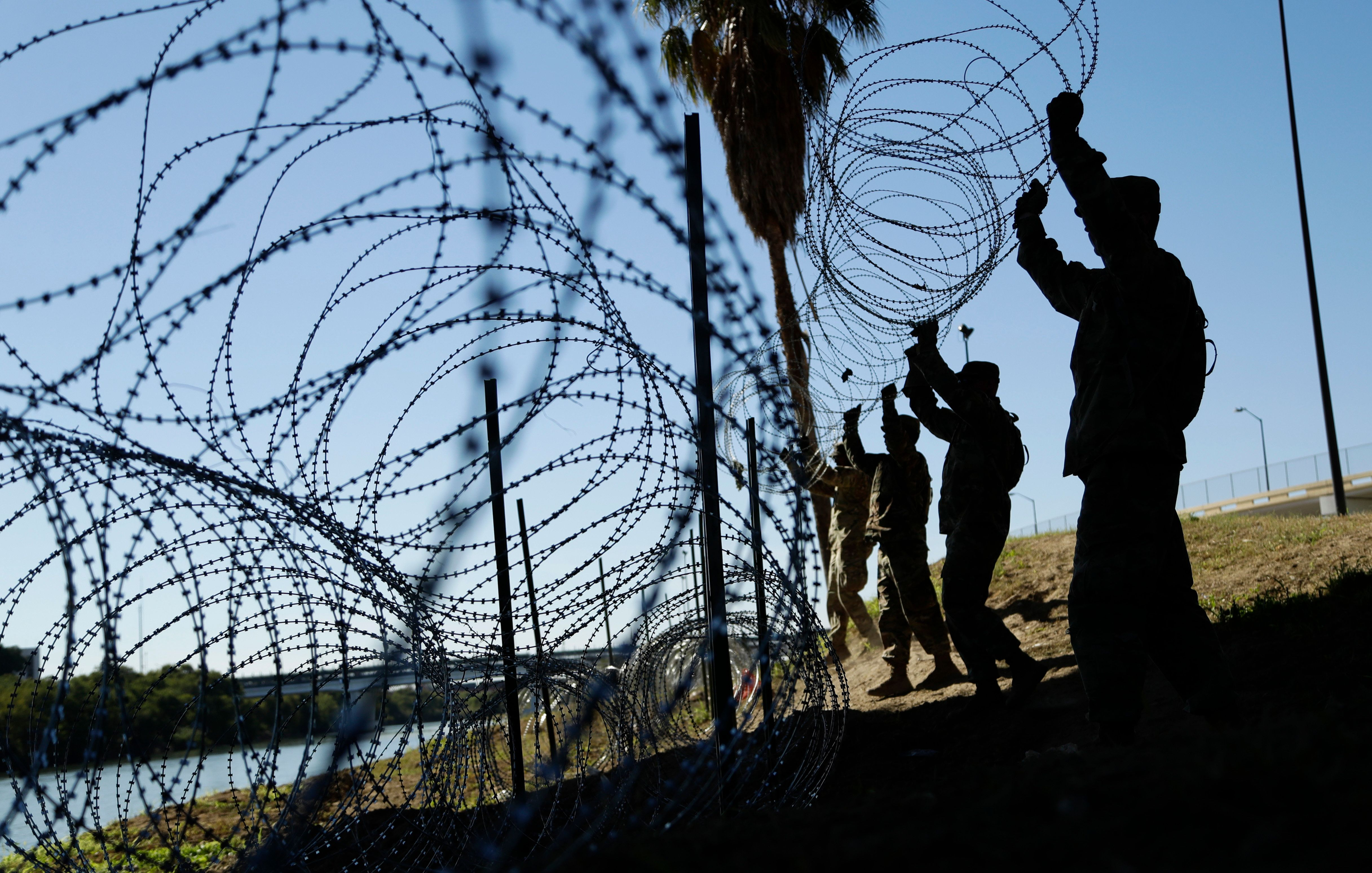 Members of the U.S. military install multiple tiers of concertina wire along the banks of the Rio Grande near the Juarez-Linc