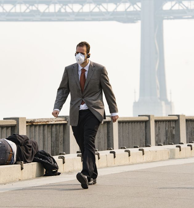A man wears a mask while another person sleeps on the ground as smoke from the Camp Fire fills the air...