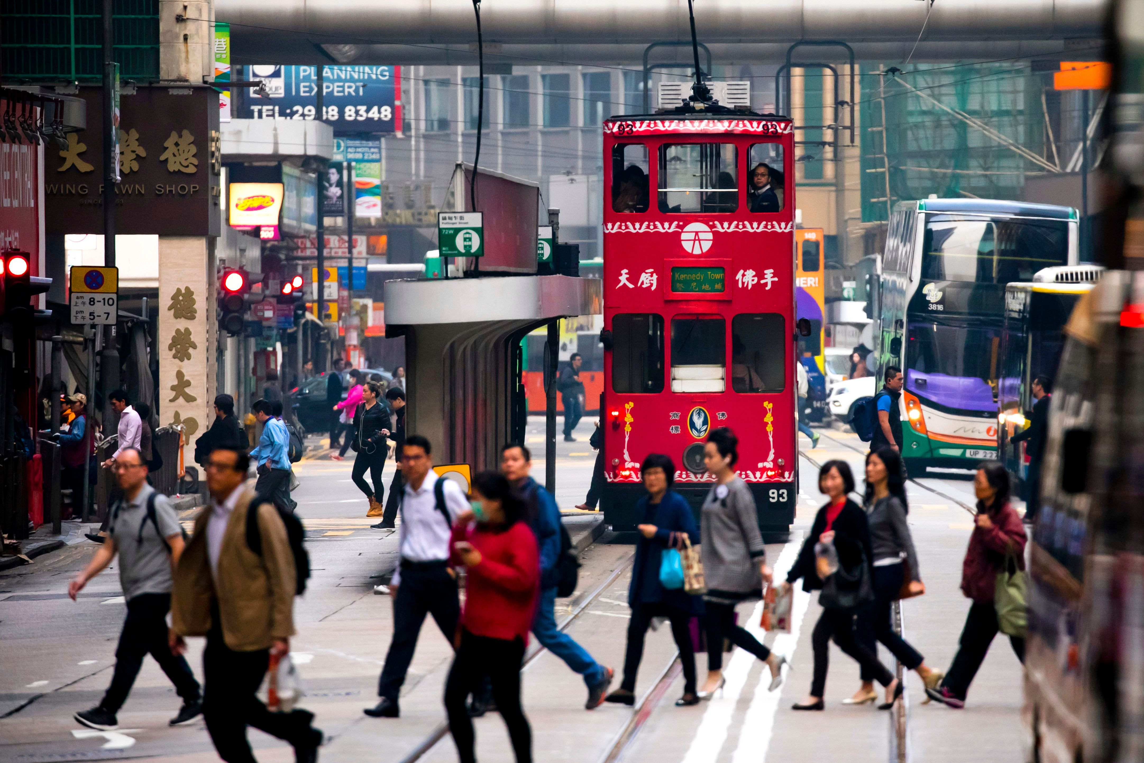 HONG-KONG, CHINA - MARCH 01: A two-storey tramway runs on 'Des Voeux Road' as pedestrians cross Central Street on March 01, 2018 in Hong-Kong, China. Hong Kong is one of the most densely populated territories in the world. (Photo by Vincent Isore/IP3/Getty Images)