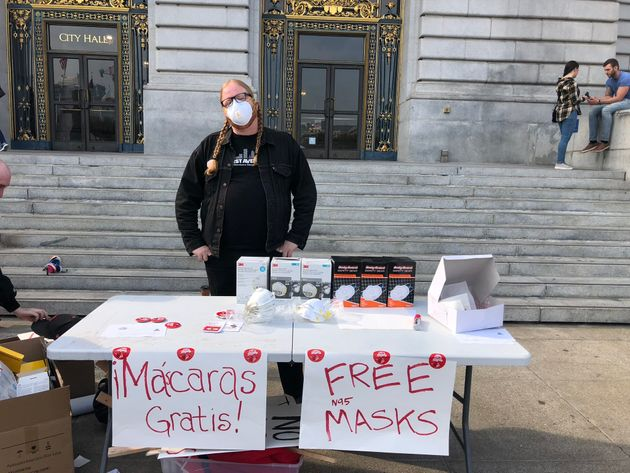 Amember of the Democratic Socialists of America distributes masks outside City Hall in San