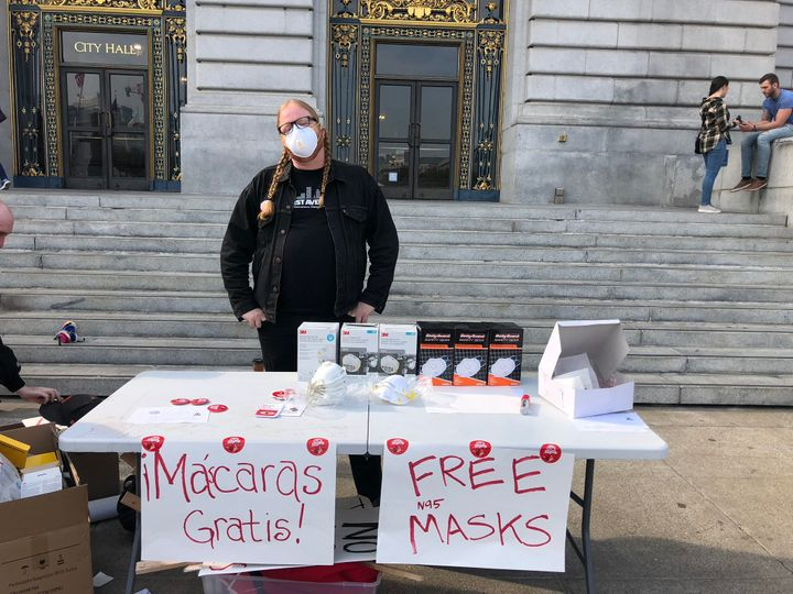 A member of the Democratic Socialists of America distributes masks outside City Hall in San Francisco.