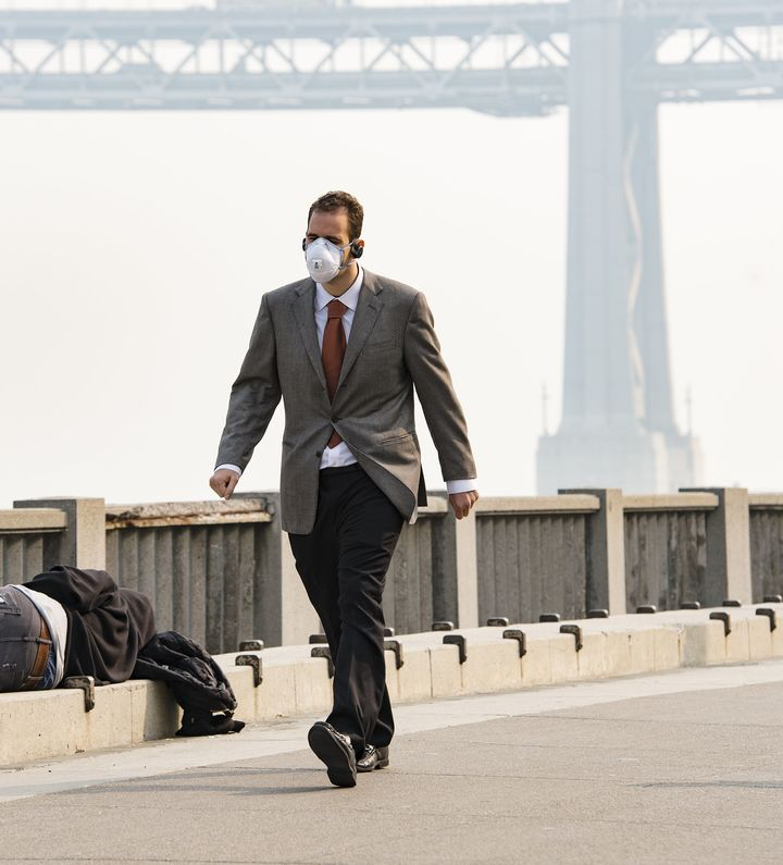 A man wearing a mask walks past a sleeping homeless person on Nov. 15 in San Francisco.