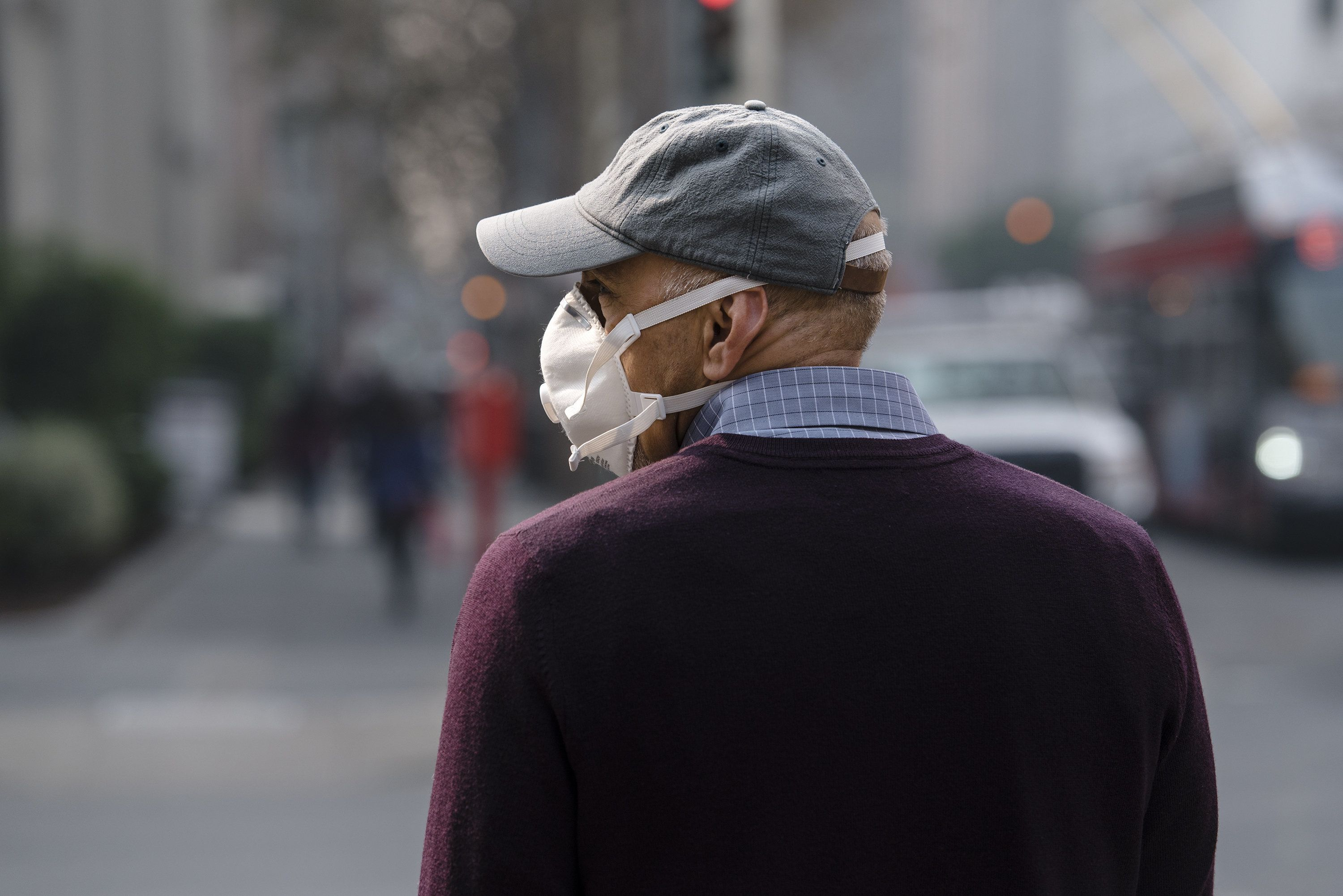 A man wears a mask while smoke from the Camp Fire fills the air in San Francisco, California, U.S., on Thursday, Nov. 15, 2018. The smoke from Californias deadliest fire is so thick that its blotting out the sun and lowering surface temperatures by as much as 10 degrees Fahrenheit (6 Celsius), according to the U.S. National Weather Service. Photographer: Michael Short/Bloomberg via Getty Images