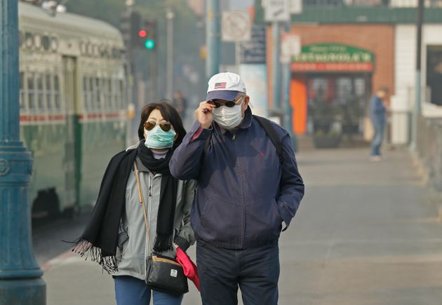 A couple wearing masks walk through San Francisco's Fisherman's Wharf amid the smoke and haze from wildfires...