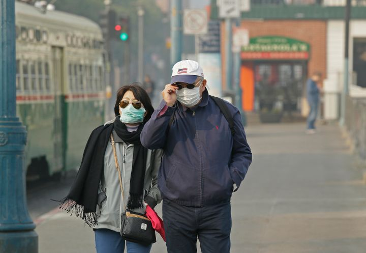 A couple wearing masks walk through San Francisco's Fisherman's Wharf amid the smoke and haze from wildfires on Nov. 16, 2018