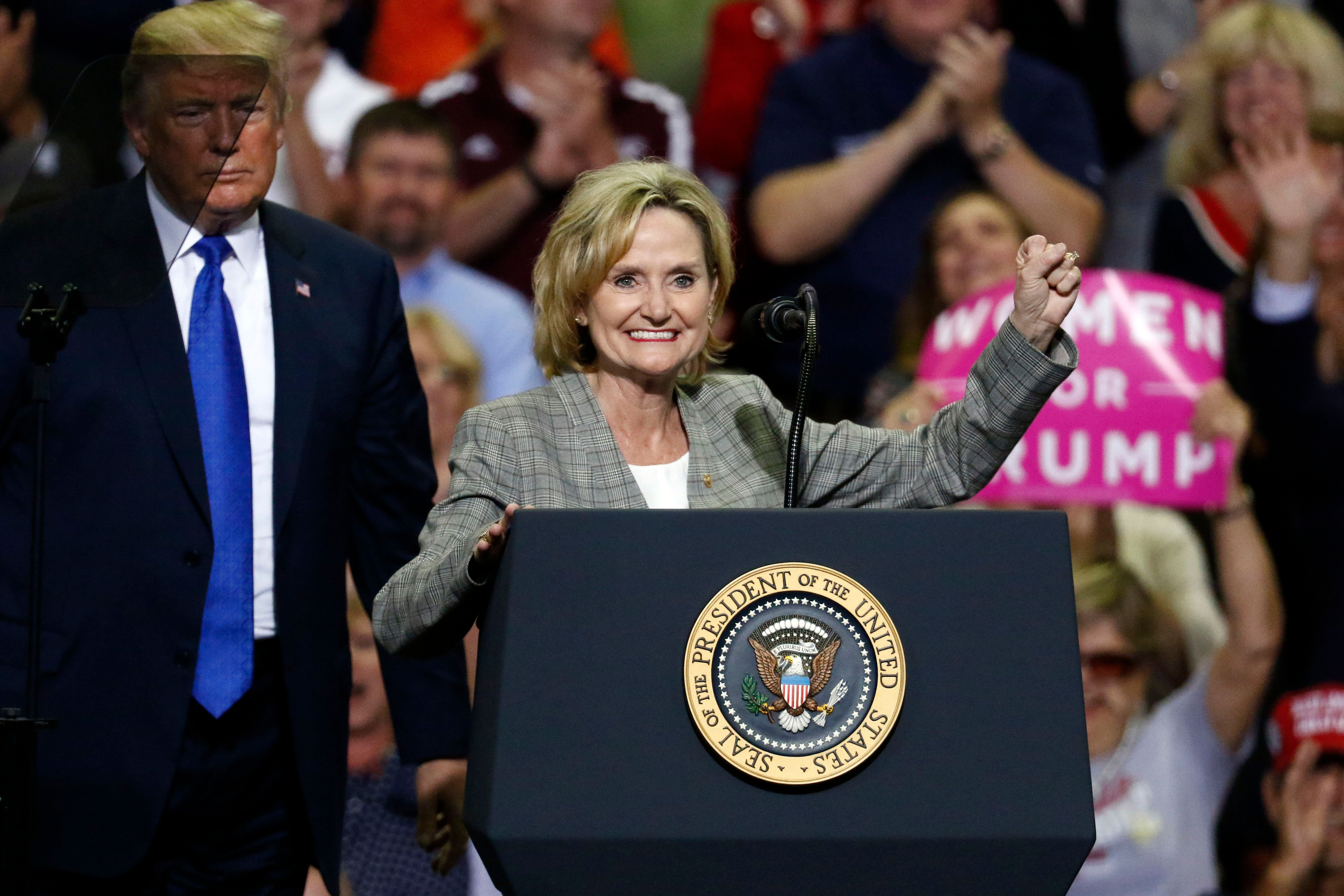 FILE - In this Oct. 2, 2018 photograph, President Donald Trump stands in the shadows while U.S. Sen. Cindy Hyde-Smith, R-Miss., encourages the crowd at a rally in Southaven, Miss. Hyde-Smith is running for the final two years of the term of former Republican U.S. Sen. Thad Cochran, who retired last year and faces three opponents in this non-partisan race, including Mike Espy, a former congressman and former U.S. agriculture secretary. (AP Photo/Rogelio V. Solis)