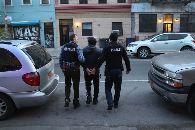 ICE officers arrest a man during a raid in Brooklyn, New