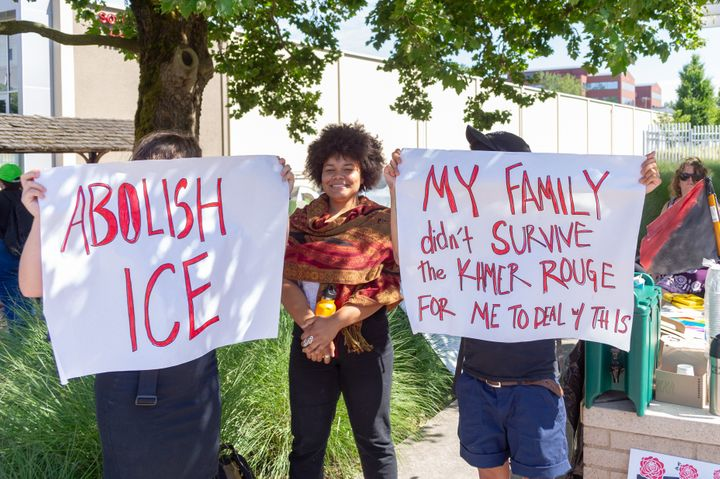 Protesters hold up signs demanding the abolition of ICE and recalling the ordeal of refugees under the Khmer Rouge regime in
