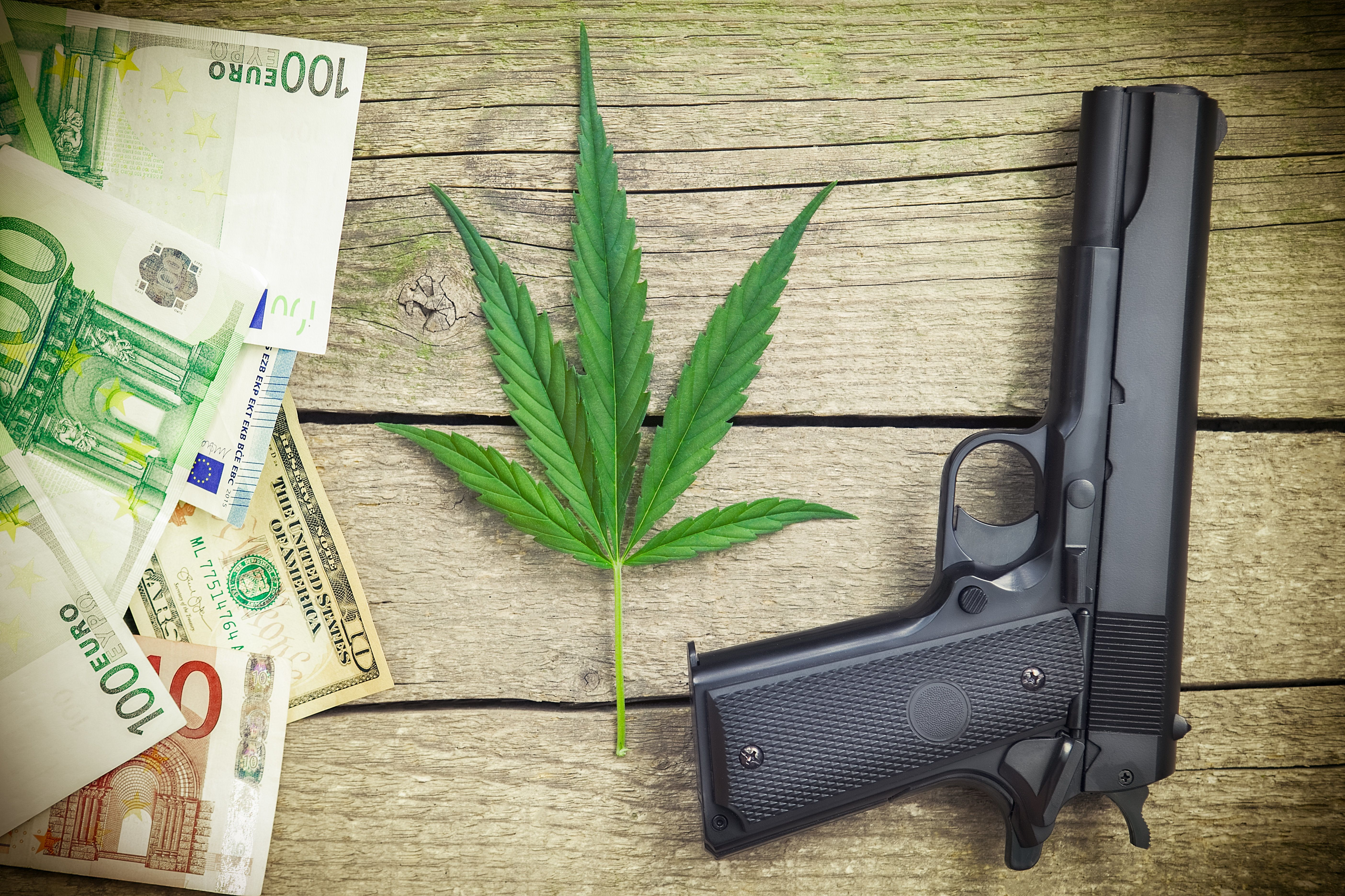 Cannabis leaf with banknotes and pistol on the table