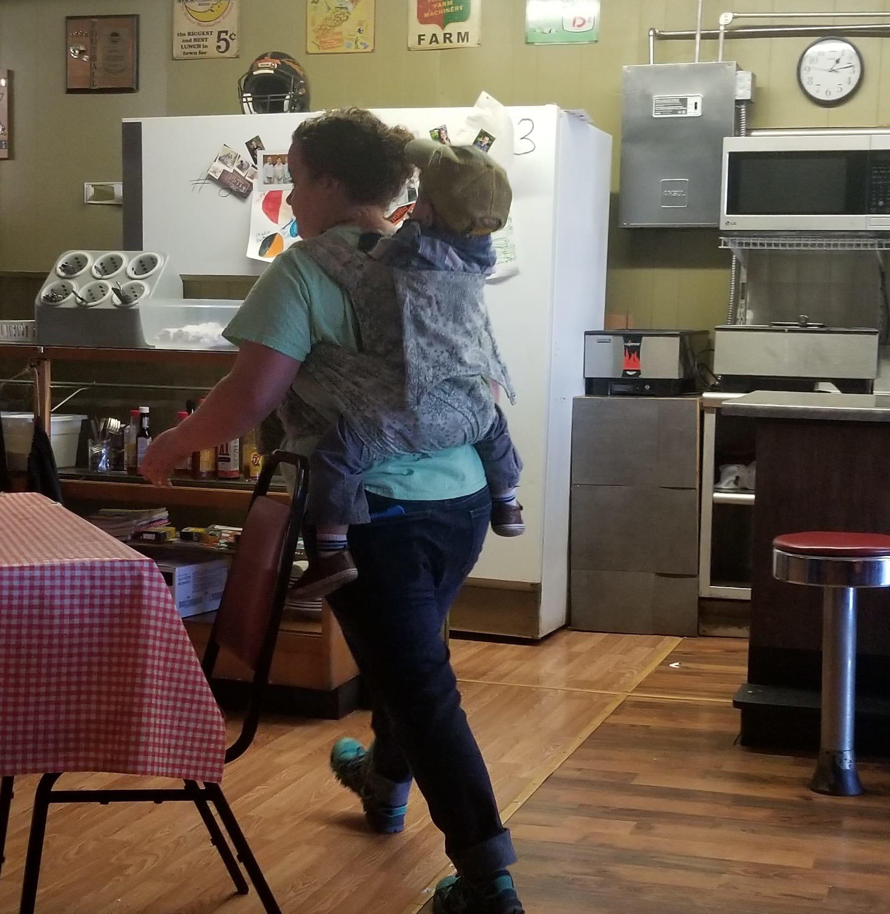Restaurant: Frau sieht Mutter mit Kind auf dem Rücken und macht ein
