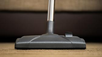 Dark head of a modern vacuum cleaner being used while vacuuming a rug. Cleaning service concept. Process of hoovering carpet with vacuum cleaner