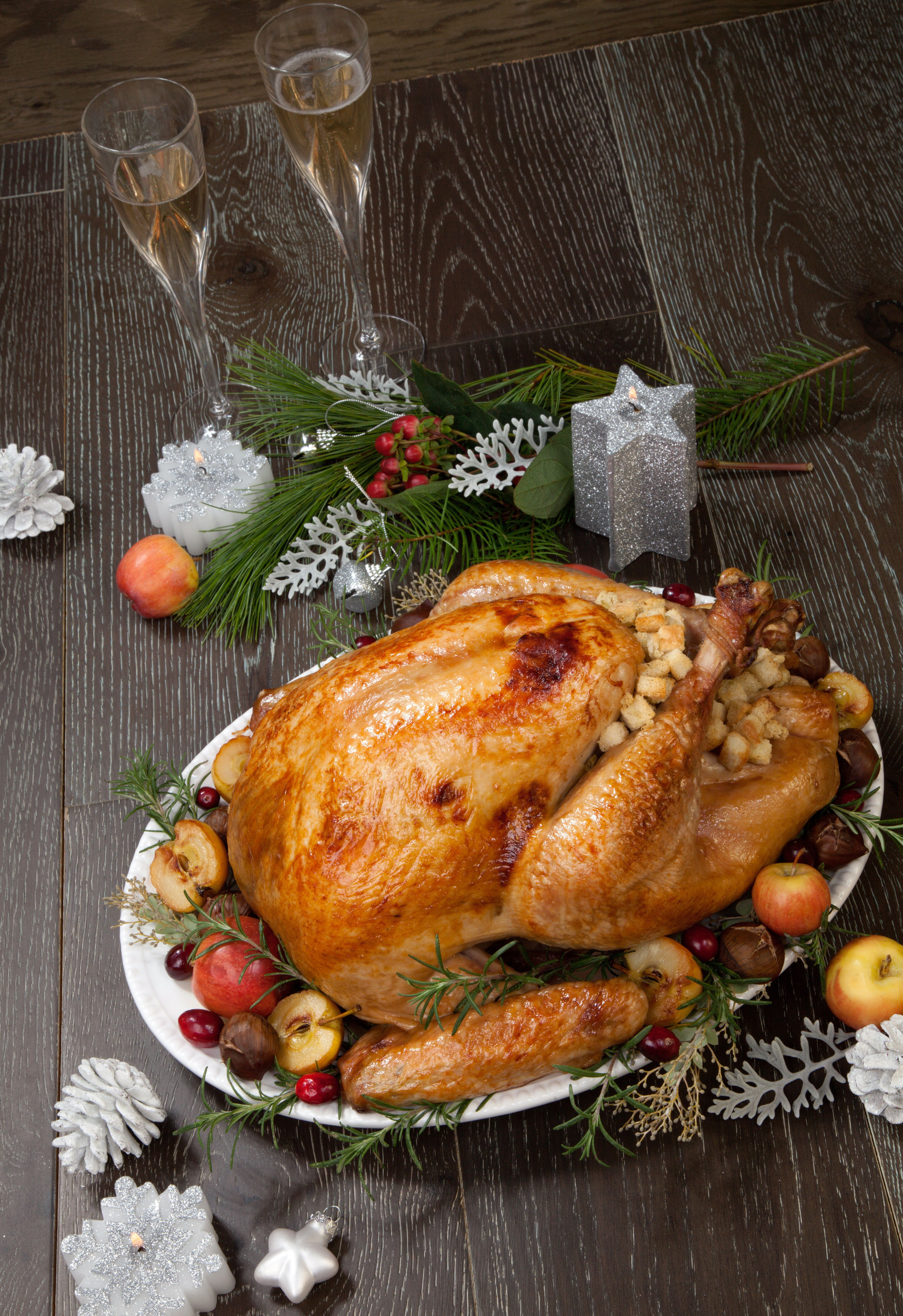 Garnished roasted Christmas turkey with grab apples, sweet chestnut, cranberry, Christmas ornaments, candles, and pine cones.'n