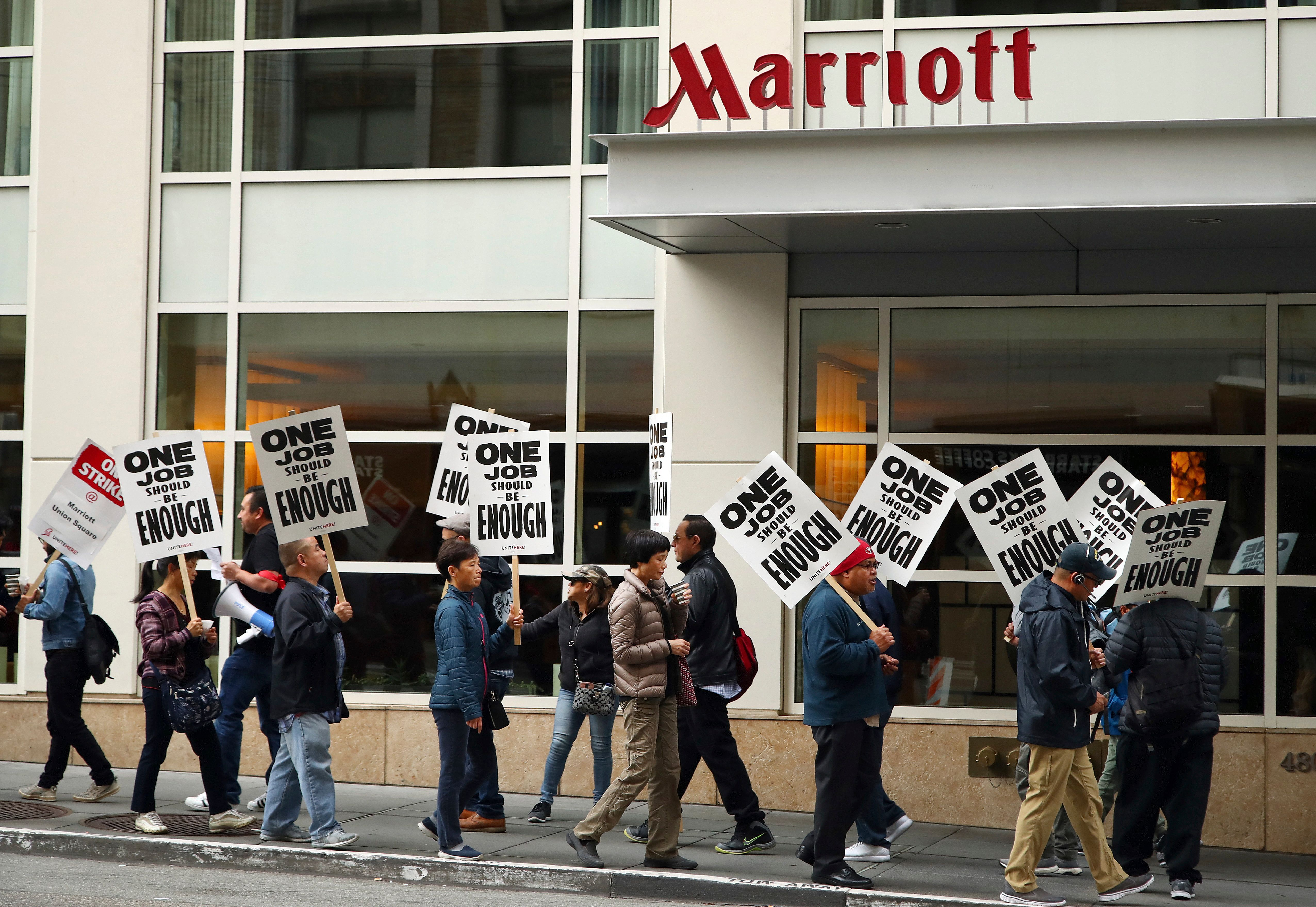 "In this Oct. 4, 2018, photo, hotel workers carrying signs that say ""One Job Should Be Enough"" strike in front of a Marriott h"