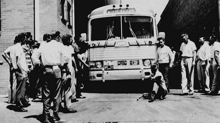 An unidentified white man sits in front of a Greyhound bus to prevent it from leaving the station with a load of Freedom Ride