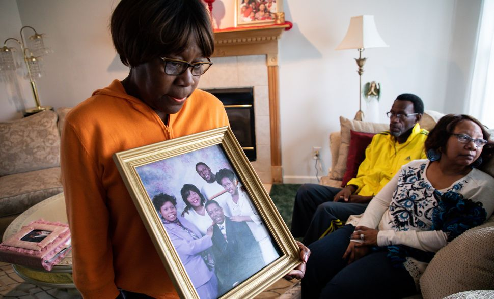 The mother of Tamara O'Neal holds a picture of her family, Nov. 20. O'Neal was fatally shot by her former fiance in Chicago t