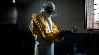 TOPSHOT - A health worker puts on his personal protective equipment (PPE) before entering the red zone of a MSF (Doctors Without Birders) supported Ebola Treatment Centre (ETC), where he will check up on patients on November 6, 2018 in Bunia, Democratic Republic of the Congo. - The death toll from an Ebola outbreak in eastern Democratic Republic of Congo has risen to more than 200, the health ministry said on November 10, 2018. (Photo by John WESSELS / AFP)        (Photo credit should read JOHN WESSELS/AFP/Getty Images)