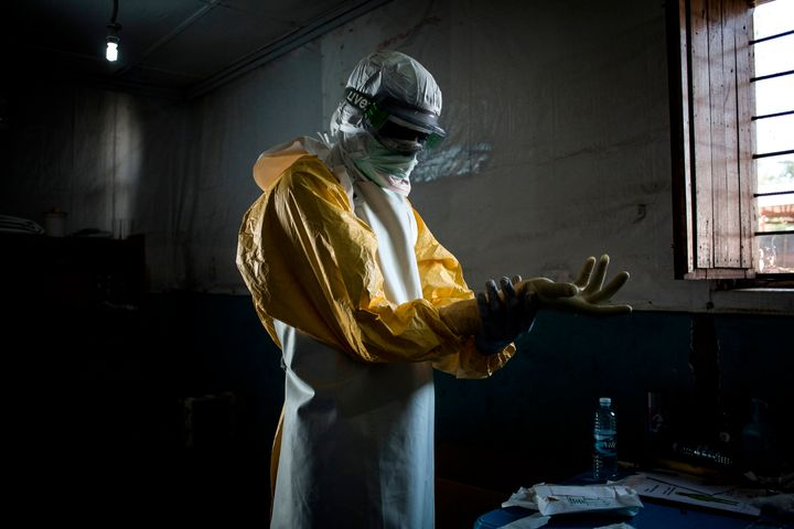 A health worker puts on protective equipment before entering the red zone of a Doctors Without Borders-supported Ebola treatm