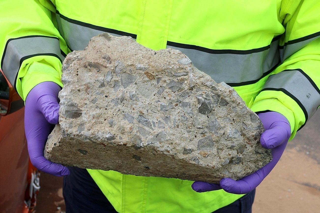 In this photo released by the Nashville Police, an officer holds large piece of concrete that struck a vehicle on Interstate 24, Tuesday, Nov. 20, 2018, in Nashville, Tenn. police believe a piece of concrete may have been thrown from an overpass and are looking for witnesses who may have seen it happen. (Nashville Police via AP)