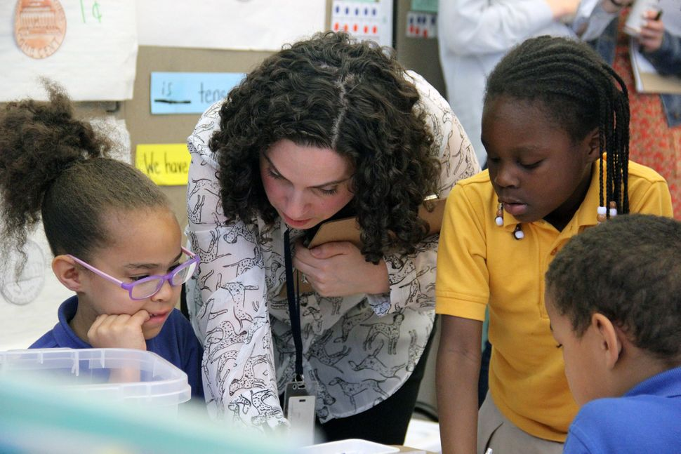 Sasha Redlener, a first-grade teacher at Mott Haven Academy Charter School, helps her students with an assignment. Classes at
