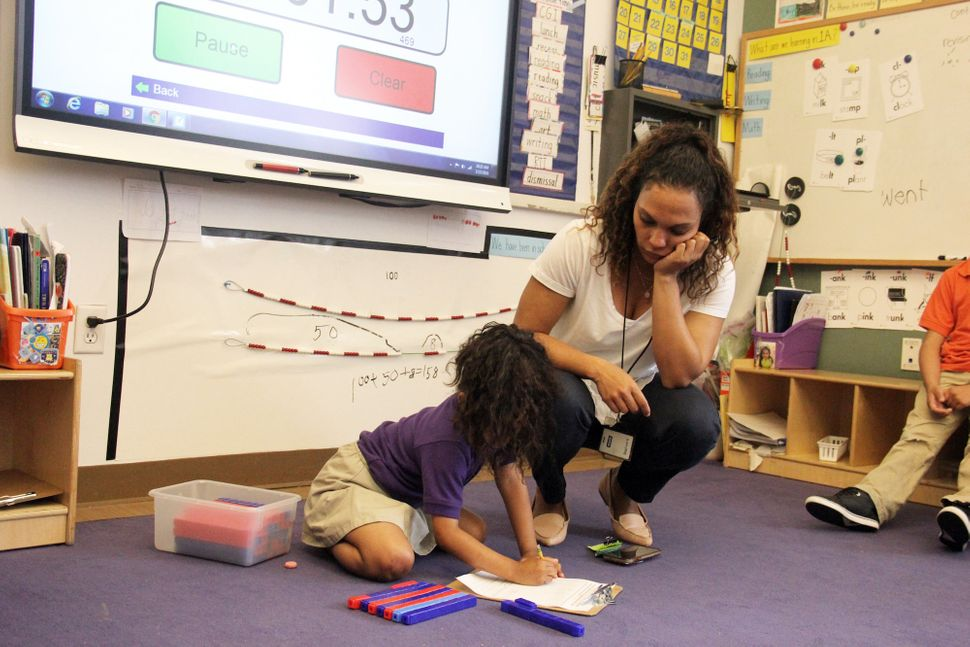 Mott Haven Academy Charter School teacher Carolina Garcia helps one of her first-grade students with an assignment. At Haven,