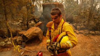 Shawn Slack rests after felling trees burned in the Camp Fire, Monday, Nov. 12, 2018, in Paradise, Calif. (AP Photo/John Locher)
