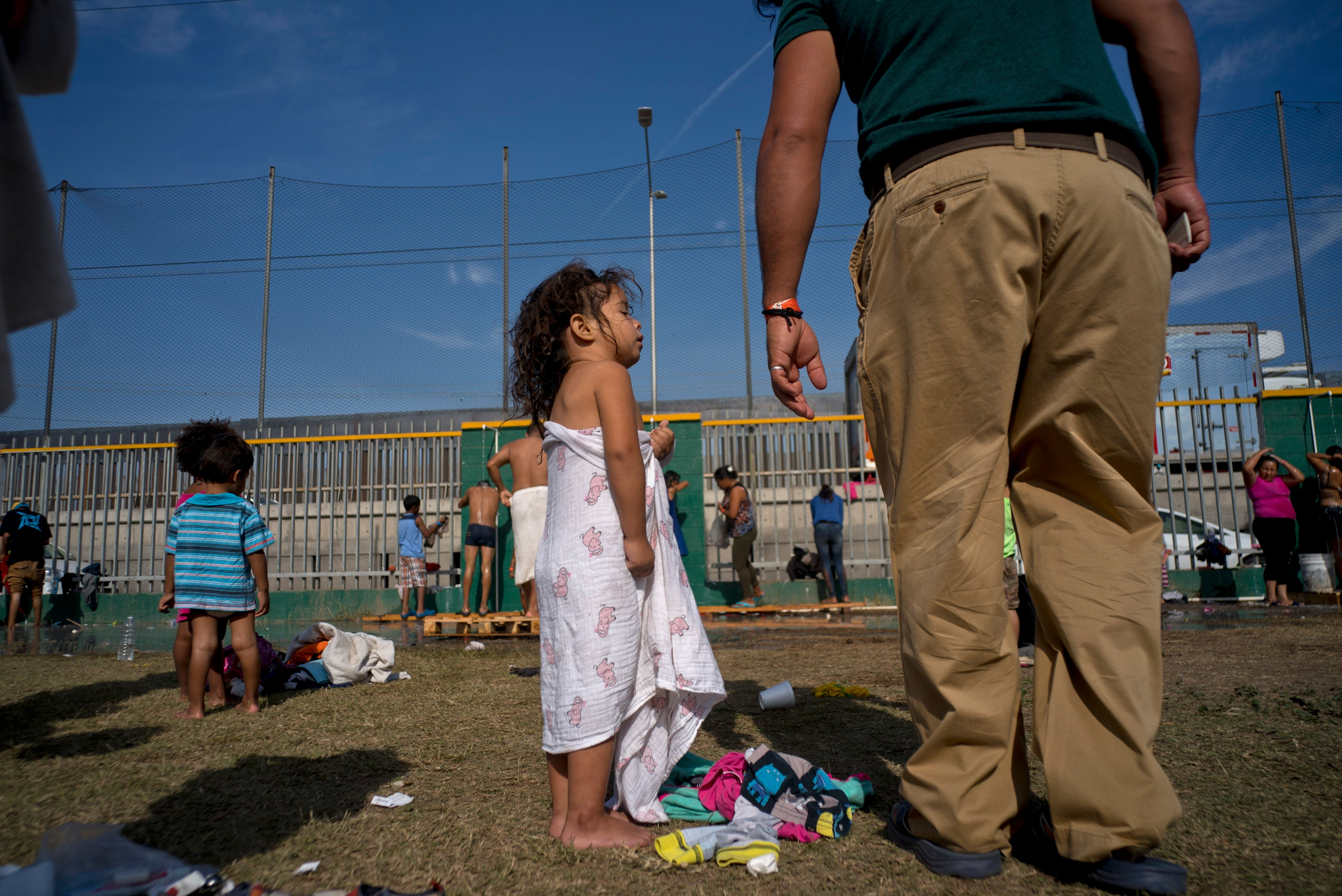 A girl traveling with the migrant caravan talks with her father after taking a bath Wednesday at a shelter in Tijuana, M
