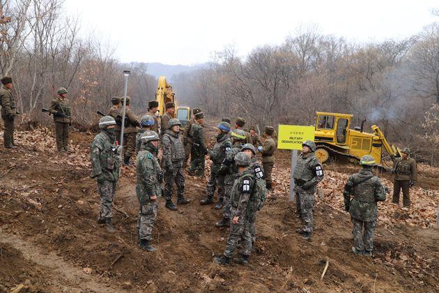 남북 군인들이 22일 중부전선 군사분계선 근처에서 만나 함께 도로연결작업을 하고