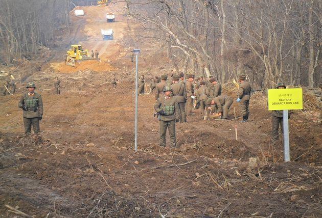 남북 군인들이 22일 중부전선 군사분계선 근처에서 만나 도로연결작업을 하고