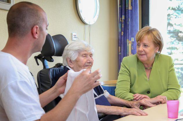 Ferdi Cebi (l.) mit einer Pflegebedürftigen und Angela Merkel (r.).