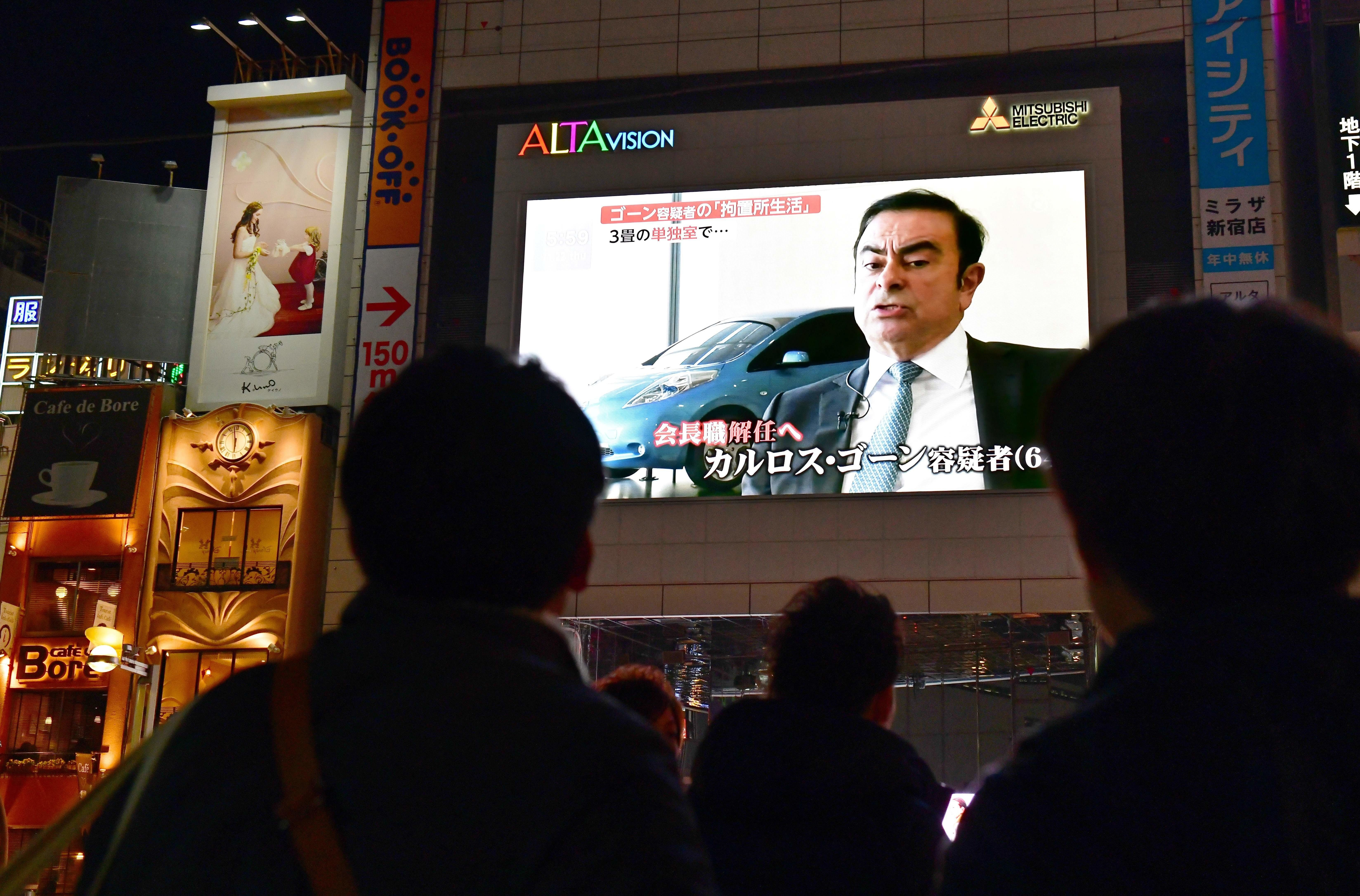 TOPSHOT - Pedestrians look at a screen showing a news programme featuring Nissan chairman Carlos Ghosn in Tokyo on November 22, 2018. - Top executives from crisis-hit Japanese car giant Nissan gathered to sack Carlos Ghosn as chairman on November 22, after his spectacular arrest for financial misconduct stunned the car industry and the business world. (Photo by Kazuhiro NOGI / AFP)        (Photo credit should read KAZUHIRO NOGI/AFP/Getty Images)