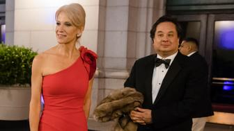 In this Thursday, Jan. 19, 2017 photo, President-elect Donald Trump adviser Kellyanne Conway, center, accompanied by her husband, George, speaks with members of the media as they arrive for a dinner at Union Station in Washington, the day before Trump's inauguration. (AP Photo/Matt Rourke)