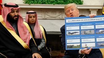 President Donald Trump shows a chart highlighting arms sales to Saudi Arabia during a meeting with Saudi Crown Prince Mohammed bin Salman in the Oval Office of the White House, Tuesday, March 20, 2018, in Washington. (AP Photo/Evan Vucci)
