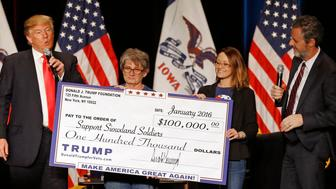 FILE - In this Jan. 31, 2016 file photo, Donald Trump, left, stages a check presentation with an enlarged copy of a $100,000 contribution from the Donald J. Trump Foundation to Support Siouxland Soldiers during a campaign event in Sioux City, Iowa., during Trump's run for president. New York Attorney General Barbara Underwood filed a lawsuit Thursday June 14, 2018, accusing Trump of illegally using his charitable foundation to pay legal settlements related to his golf clubs and to bolster his presidential campaign with Foundation disbursements such as this one in Iowa. Also pictured is Jerry Falwell, Jr., right, president of Liberty University. (AP Photo/Patrick Semansky, File)