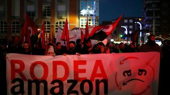 "People shouts slogans during a strike in Torrejon Ardoz, Spain, Friday, Nov. 23, 2018. Amazon workers are staging a two-day strike coinciding with Black Friday over a labour dispute. Banner reads in Spanish: ""Surrounds Amazon"". (AP Photo/Manu Fernandez)"