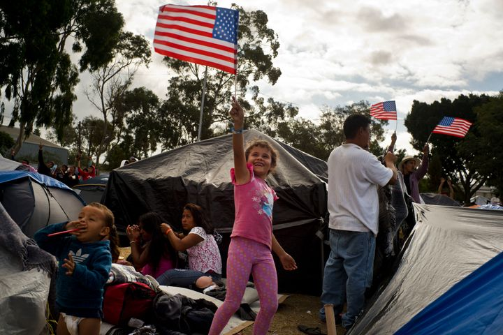 Seven-year-old Honduran migrant Genesis Belen Mejia Flores waves an American flag at two U.S. border control helicopters flyi
